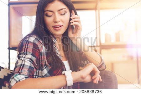 Time is money. Beautiful brunette wearing casual attire looking at a wrist watch for time checking while sitting on a sofa and having a serious business call.