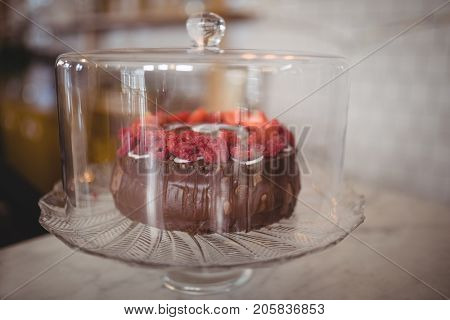 Close up of fresh raspberry cake in glass container on table at coffee shop
