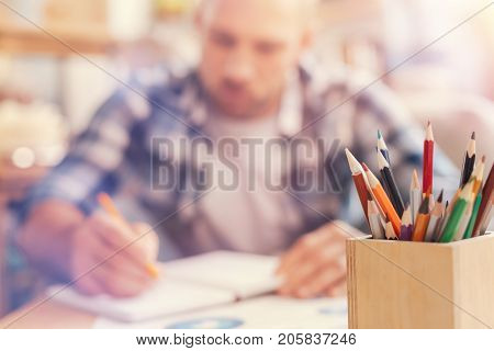 Creative workspace. Selective focus on a wooden jar with multi colored pencils standing on a table while a serious self employed man writing something down while working in the background.