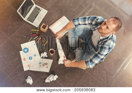 Lack of ideas. Top view on a young startupper in casual sitting on the floor and looking into vacancy while struggling with business project implementation.