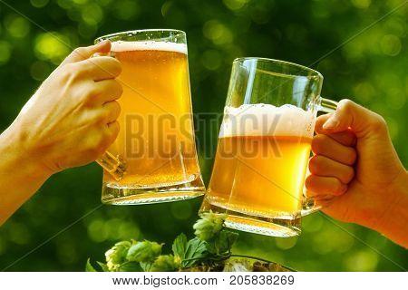 Oktoberfest fun cheers beer mugs in hands Man and woman on outdoor