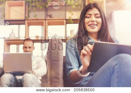 Young business generation. Low angle shot of a beaming young businesswoman in casual surfing internet on her digital tablet while sitting on a sofa and working next to a male colleague