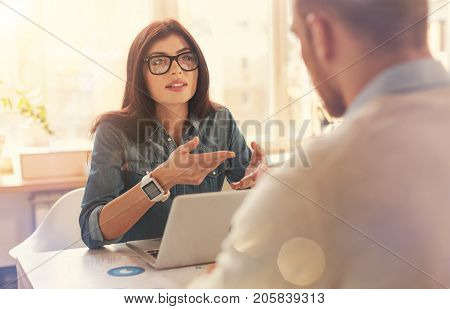 Do you understand. Selective focus on a millennial businesswoman wearing glasses sitting at a table and gesturing while talking to a business mate during an informal meeting.