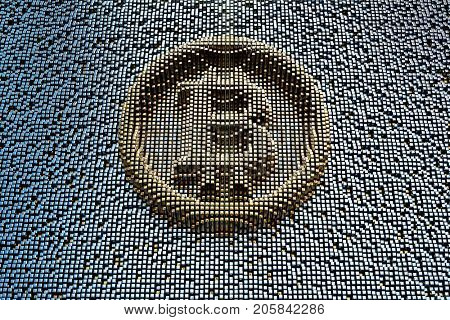 Symbol bitcoin from golden small cubes, towering above the background of black small cubes.