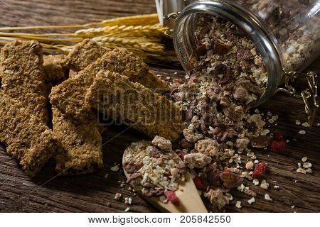 Granola bars and breakfast cereals spilling out of bottle on wooden table