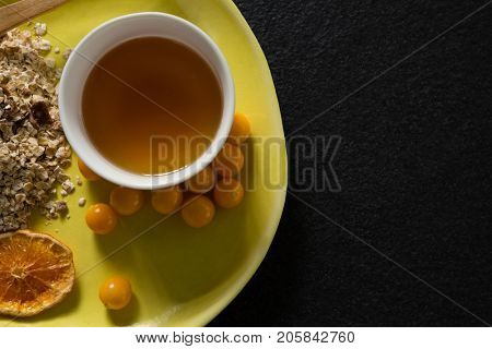Close-up of dried orange slice, oatmeal, golden berry and maple syrup in plate