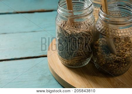 Jar with various breakfast cereals on wooden table