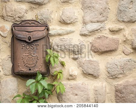 antique brown rusty mailbox on a stone made wall