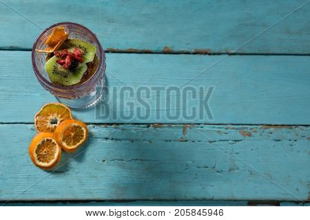 Kiwifruit slice and dried fruits in glass bowl with dried orange slice on wooden table