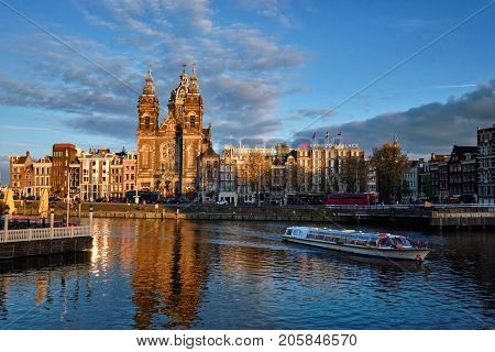 AMSTERDAM, NETHERLANDS - MAY 9, 2017: Tourist boat in Amsterdam canal and Church of Saint Nicholas (Sint-Nicolaaskerk) on sunset. Amsterdam, Netherlands