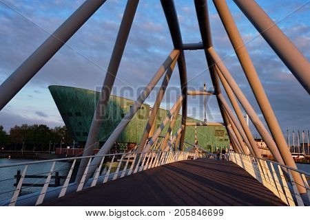 AMSTERDAM, NETHERLANDS - MAY 9, 2017: NEMO Science museum and Mr. J.J. van der Veldebrug bridge. It is the largest science center in Netherlands with over 500000 visitors per year