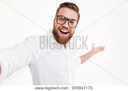 Close up portrait of a happy cheerful bearded man presenting copy space on his palm isolated over white background