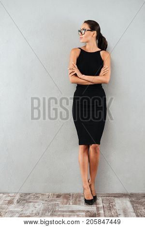 Full length portrait of a pretty young businesswoman in black dress and eyeglasses standing and looking away at copy space isolated over gray background