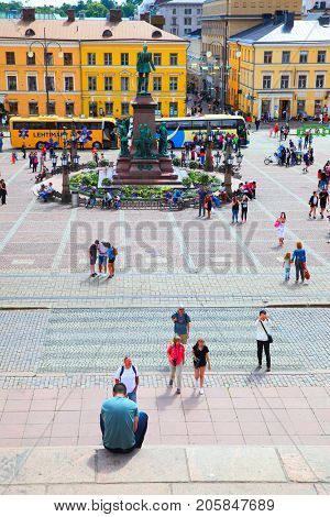 Helsinki, Finland - July 26, 2017: Senate Square and people sitting on stairs in Helsinki