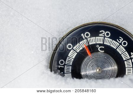 Vintage thermometer with celsius scale showing low temperature placed in fresh snow