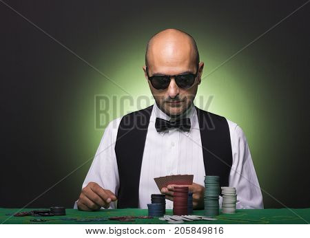 Pensive poker player looking to his cards at the table