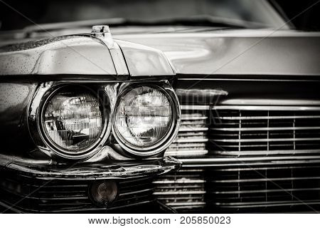 Close up detail of restored classic American car. Focus on headlights and hood. Retro vehicle in black and white.