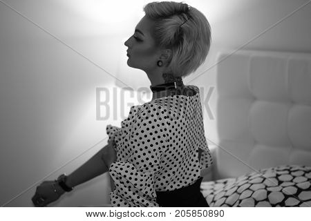 Attractive alluring young blond woman with short haircut on bed in bedroom, black and white, indoors, from the back