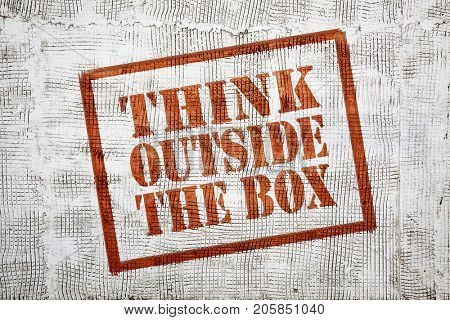 think outside the box - graffiti sign with arrow on stucco wall