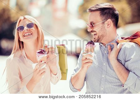 Cheerful young couple eating ice cream.Image of a lovely couple eating ice cream in the city.