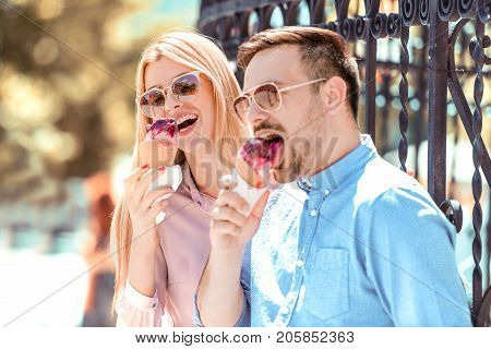 Cheerful young couple eating ice cream.Image of a lovely couple eating ice-cream in the city.