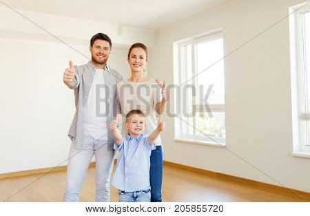 mortgage, people, housing and real estate concept - happy family with child moving to new home and showing thumbs up
