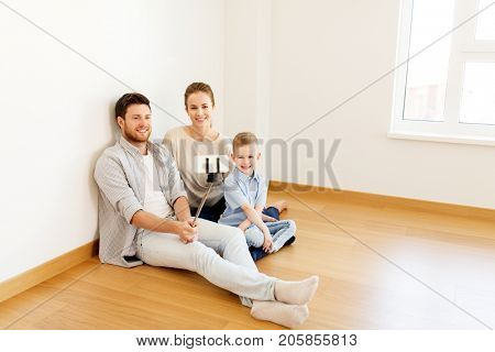 mortgage, people, housing and real estate concept - happy family with child taking picture by smartphone selfie stick at new home