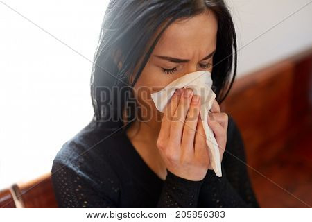 burial, people, grief and mourning concept - close up of unhappy crying woman blowing nose with wipe at funeral day