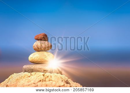 Zen balanced small pile of stacked stones on the beach in summer