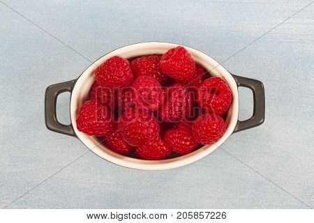 Fresh red Raspberry on bright bue background