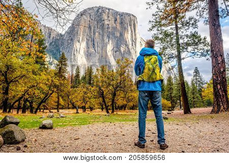 Tourist with backpack hiking in Yosemite National Park Valley at cloudy autumn morning. Low clouds lay in the valley. California, USA.