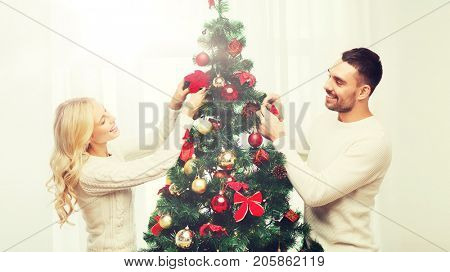 family, x-mas, winter holidays and people concept - happy couple decorating christmas tree at home