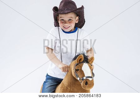 Kids Consepts. Portrait of Happy Smiling and Glad Caucasian Little Boy in Cowboy Clothing With Symbolic Plush Horse Against White. Horizontal Image Composition