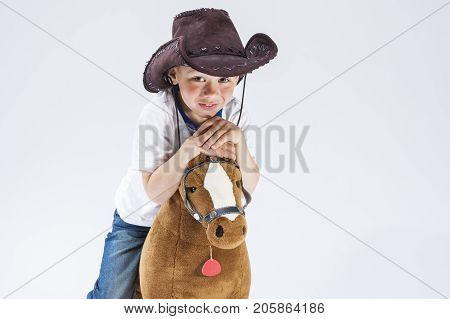 Natural Portrait of Happy Smiling and Glad Caucasian Little Boy in Cowboy Clothing With Symbolic Plush Horse Against White. Horizontal Composition