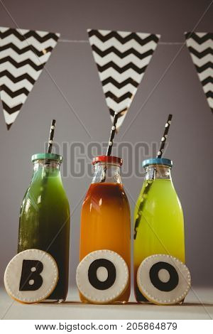 Cookies with boo text by colorful drinks in bottles against gray background