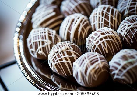 Creamy and chocolate cake balls covered with vanilla icing on a silver platter.