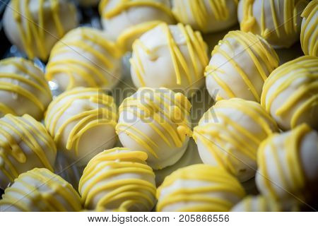 Creamy lemon vanilla cake balls covered with yellow icing on a silver platter.
