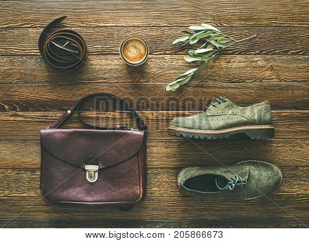 Flat-lay of woman's fall accessories and coffee. Haki suede oxford boots, brown shoulder bag, leather belt and cup of espresso over wooden background, top view