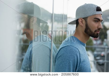 Thoughtful man leaning on glass