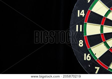 Partial red green black and cream dartboard on black with copyspace on left.