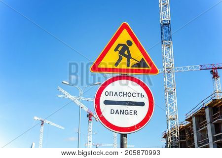 Warning signs about repair work on the city street. Roadwork sign and Danger sign close up.