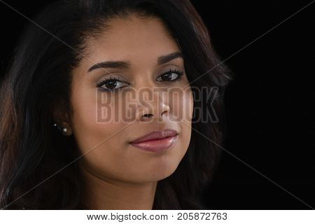 Close up portrait of confident woman against black background