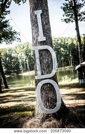 Homemade blinged out wedding sign hanging on a tree.