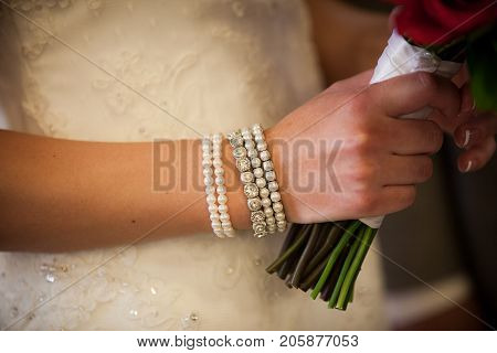 Close up of classy ivory bracelet on the wrist of a beautiful bride.