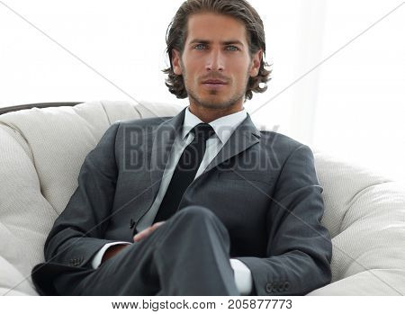 confident businessman sitting in a large comfortable chair.