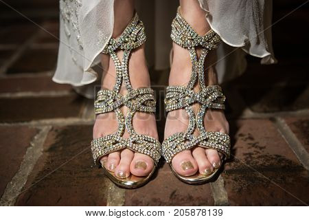 Close Up of Asian bride's diamond studded shoes standing on a brick floor.