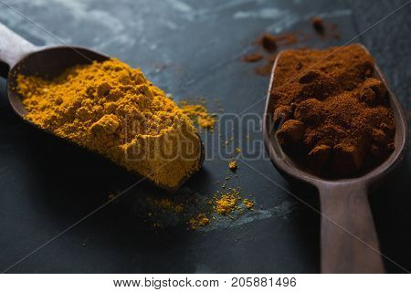 Close-up of turmeric powder and chili powder on wooden spoon