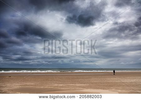 Stormy sky over the beach at Havre Aubert, Iles de la Madeleine, Canada. A small solitary figure can be seen walking close to the waves.