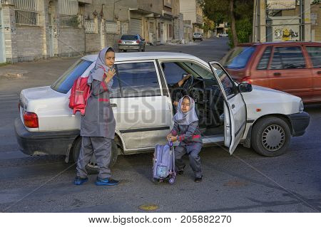 Fars Province Shiraz Iran - 19 april 2017: Two schoolgirls in uniform come out of a car and put on school bags near their school.