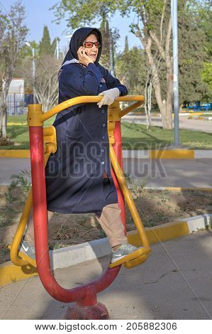 Fars Province Shiraz Iran - 19 april 2017: Mature Muslim woman in hijab during a morning workout at the gym outdoors.